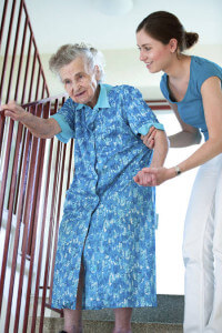 caregiver-with-elderly-woman-on-stairs