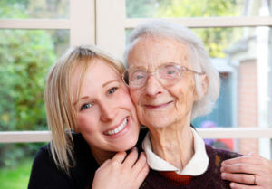 senior woman with female caregiver hugging