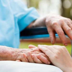 South Shore home care aide holding hand of elderly woman